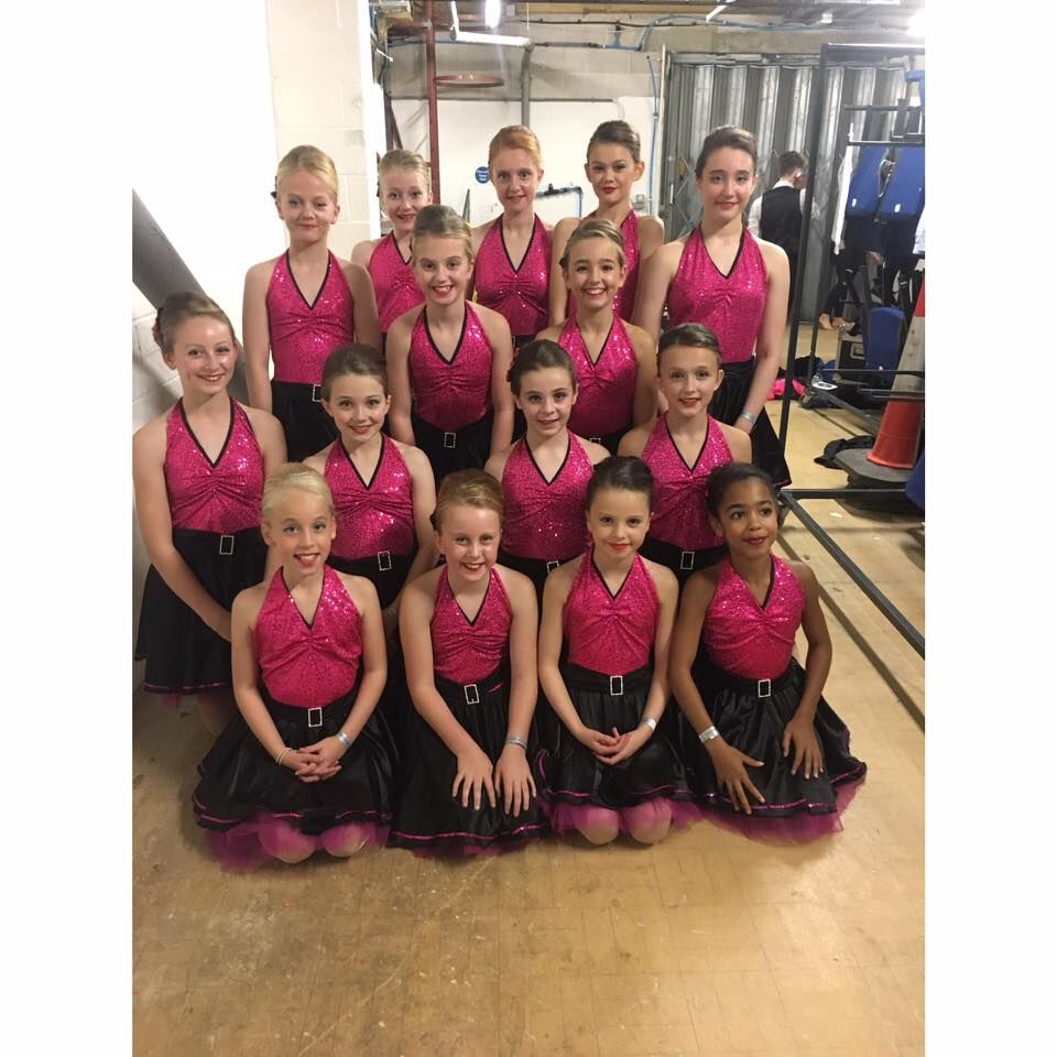 group of girl dancers dressed in pink and black
